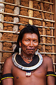 A-Ukre Village, Brazil. Portrait of Kryt, a Kayapo man with black face paint, bead and shell adornment with wattle and daub wall.