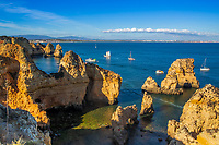 Boats on the pristine turquoise waters of the famous Ponta da Piedade cliffs, with beautiful, golden sunset light, in Algarve region, Portugal Europe