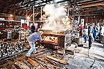 Worker Feeds firewood into the evaporator