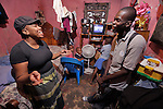 """Clifford Blaise (right) is a psycho-social monitor for the Social Mission of the Haitian Church (MISSEH), which has helped 1200 people move out of the crowded Prophecie camp for survivors of the devastating January 2010 earthquake. Among them is Yvette Chery (left) and her three boys, seen here living in their one-room apartment in Port-au-Prince which they abandoned after the quake. MISSEH has accompanied Chery and other families returning to their damaged former homes, helping them deal with fear that the earth will start trembling once again. """"We helped them understand that they were better off at home than dealing with the constant problems in the camps,""""  he says. """"I am still afraid, though not every day. I'm trying to live with it,""""  she says. Blaise leads the program' s hygiene emphasis, which has taken on new urgency with last year's cholera outbreak. """"Our main message was ' Wash your hands, wash your hands, wash your hands. After using the toilet, wash your hands. After shaking hands, wash your hands. After cleaning the baby, wash your hands. It's pretty simple. And we have had very few cases of cholera,"""" he says.  MISSEH's work is supported by Norwegian Church Aid and Church World Service, members of the ACT Alliance."""