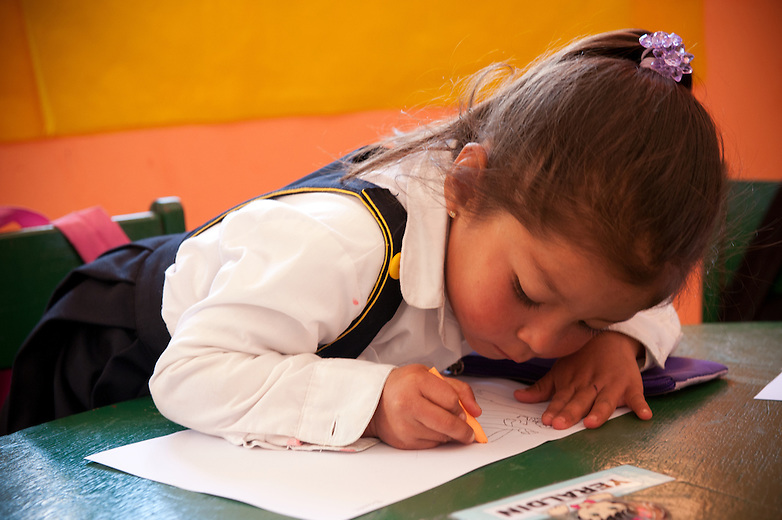 """A young student in the Kindergarten class gets excited when a guest asks her to draw a picture of her family. Although there is somewhat of a language barrier between the guests and the students, the word """"familia"""" is mutually understood. Peruvian kids are happy to share because their culture prides itself on the importance of family and community."""