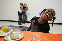 Dyamond Poindexter, 8, laughs hysterically as she enjoys a Thanksgiving meal with friends during the 3rd annual Boys & Girls Club of Charlottesville Thanksgiving dinner held Tuesday night at Buford Elementary School. The meal is donated by the Wood Grill bringing club members and their families together. The evening includes a raffle and fun games for the kids. Photo/The daily Progres/Andrew Shurtleff
