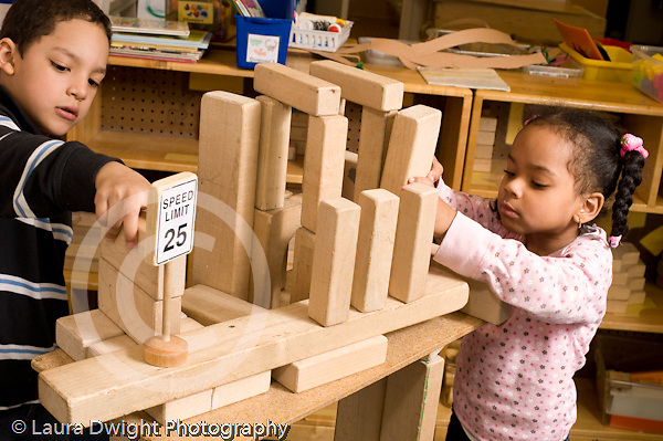 Preschool 4-5 year olds block area children playing with wooden blocks boy and girl working on tall structure together horizontal