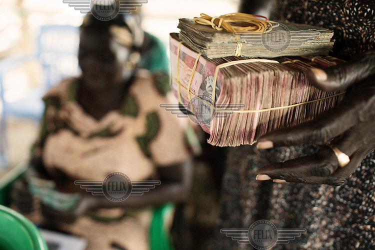 A woman caries a block of bank notes collected from people attending a meeting of a village saving group (VSLA).