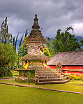 A shrine stands in the landscaped lawn in the grounds of the Hindu temple of Ulun Danu at Candikuning is one of the iconic images of Bali, Indonesia.  Located in the high hills of the Bedugul, about 30 miles north of Bali's capital city of Denpasar, the temple is built on the shores of the crater Lake Bratan (formed from the sunken crater of a long-dormant volcano).  Much of the inner precincts of the temple is closed to the (non-Hindu) public, but the gardens are spectacular and feature fabulous shrines, statuary, and views.  (HDR image)