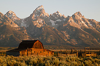 The historic John Moulton barn and farm on Mormon Row, with the Teton Range in the background at sunrise, in Grand Teton National Park, Wyoming, USA