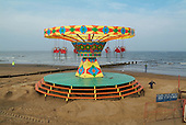 Merry-go-round on the beach at the seaside holiday resort of Cleethorpes, on the outskirts of the declining fishing port of Grimsby.