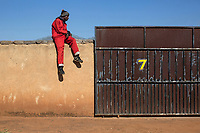A member of the Red Ants sits on the wall of a house from where the occupants are being evicted.<br /><br />The Red Ants are a controversial private security company often hired to clear squatters from land and so-called 'hijacked' properties.