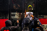 Radical students of the Universidad Nacional de Colombia attach a poster to a bus window during a protest march against government's policies and corruption within the public educational system in Bogotá, Colombia, 24 October 2019.