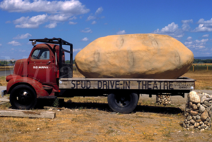 A giant, artificial potato sits on the bed of a bright red truck advertising the Spud Drive-in Theatre in Boise. Boise Idaho.