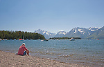 Jackson Lake at Leeks Marina.  Best pizza in a remote location.  Grand Teton National Park, United States, Wyoming.  Woman relaxing on beach.