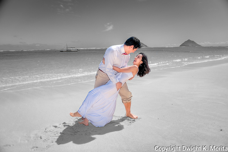 Asian bride and groom dance and dip while they stroll on Lanikai beach as they look forward to their life as a married couple following their wedding. Color and BW cutout.
