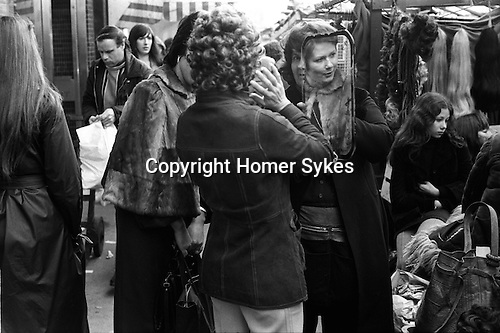 """Tower Hamlets, London. 1975<br /> Down the Roman, a chic East Ender tryies on a fashionable curly wig, """"does it look OK"""", she asks her friend who's wearing a stylish fur cape with collar, """"yeah it looks fab"""", the friend smiles back."""