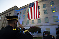 Officers salute an American flag unfurled over the side of the Pentagon at sunrise on the 20th anniversary of the 9/11 terrorist attacks at the Pentagon September 11, 2021 in Arlington, Virginia. <br /> CAP/MPI/RS<br /> ©RS/MPI/Capital Pictures