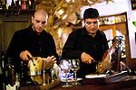 Waiters carve cured legs of pork or prosciutto crudo, at Osteria della Gensola restaurant in Trastevere.