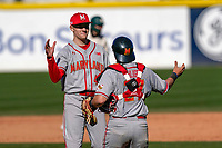 Freshman pitcher Jason Savacool (45) of the Maryland Terrapins, making his collegiate debut, pitched a complete-game 3-2 win against the Michigan State Spartans on Sunday, March 7, 2021, at Fluor Field at the West End in Greenville, South Carolina. Here he slaps hands with catcher Luke Shliger (27) after the final out. (Tom Priddy/Four Seam Images)
