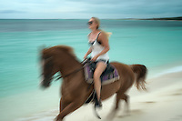 Woman galloping horse on shore. Turks and Caicos. Providenciales