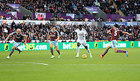 Pictured: Bafetimbi Gomis of Swansea (3rd L) takes a shot off target, against L-R James Collins, Stewart Downing and James Tomkins of West Ham Saturday 10 January 2015<br /> Re: Barclays Premier League, Swansea City FC v West Ham United at the Liberty Stadium, south Wales, UK