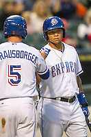 Round Rock Express outfielder Michael Choice (20) congratulates teammate Ryan Strausborger (5) after he scored during Pacific Coast League game against the Memphis Redbirds on April 21, 2015 at the Dell Diamond in Round Rock, Texas. Round Rock defeated Memphis 2-1. (Andrew Woolley/Four Seam Images)