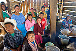 A group of Guatemalans pose inside a covered cooking area, preparing a meal for a religious holiday, San Nicolas, Western Highlands, Guatemala