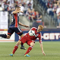 Chicago Fire midfielder Jeff Larentowicz (20) blunts New England Revolution forward Chad Barrett (9) attack. In a Major League Soccer (MLS) match, the New England Revolution (blue) defeated Chicago Fire (red), 2-0, at Gillette Stadium on August 17, 2013.
