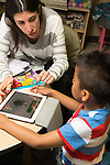 Education Preschool 4-5 year olds teacher therapist working with boy using iPad tablet