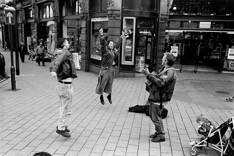 © John Angerson.Armed with tambourines and songbooks, members begin an impromptu celebration of their faith in the main shopping area of Leeds.