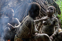 Pygmy girls paint each other in support of their brothers who are going thru a manhood initiation ceremony.  These folks all had shelter for the night in about two hours.  Women bend the branches to create a superstructures and then go off in the woods to get the right kind of leaves.  The Forest Hunting camps we hiked to are about 10k to the camp and then another 10K to where they string their nets.   Boys who are going thru the end of the circumcision ceremony called Kumbi accompanied the pygmies to the camp and were housed off to the side.  They were whipped every morning and then sent off into the forest to hunt or fish.