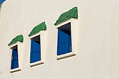 Essaouira, Morocco. Windows with blue painted shutters and green tiled canopies.