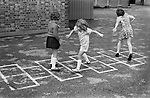 Primary school playground. Girls playing hopscotch. South London. 1970s Britain...