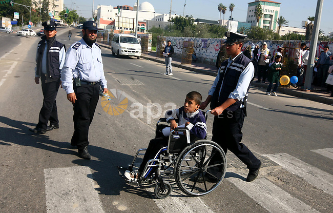 Palestinian policemen help a wheelchair-bound boy to cross a street in Gaza City during a gathering of people with special needs to mark the International Day for Persons with Disabilities on Dec. 03, 2011. Photo by Majdi Fathi