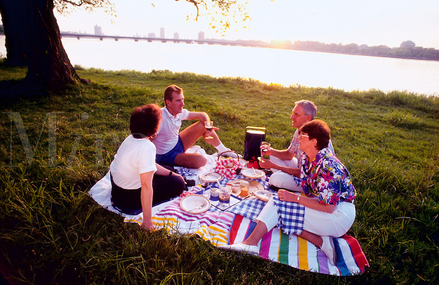 Two middle-aged couples have a picnic on the Esplanade along the Charles River. Boston, Massachusetts.
