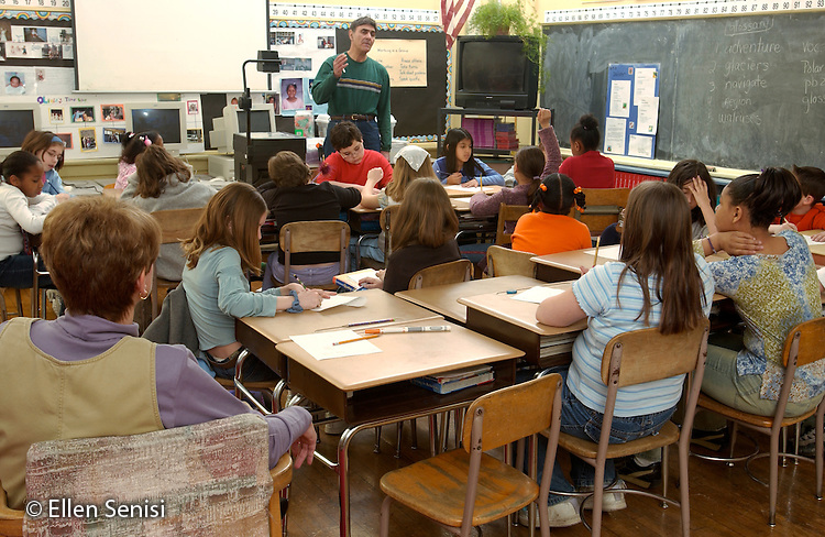 """MR / Schenectady, NY.Yates Arts-in-Education Magnet School (urban elementary school) .Grade 4 .Students in class review session for math standardized test with math resource teacher using overhead projector..New York State fourth grade students are evaluated in 3 subjects (math, language arts, science) statewide. (They are also evaluated in early fifth grade on social studies material learned in fourth grade.)  Results of State Assessments are used to prepare Report Cards on the effectiveness of individual schools and of school districts. A """"failing"""" school can be put on probation and, if it does not improve, have its state aid taken away. Exams are graded 1 through 4; 1 is a failing grade, 2 indicates the student is """"at risk """". Unfunded mandate requires schools to provide AIS (Academic Intervention Services) to at-risk students..MR: g4m   Meo1.©Ellen B. Senisi"""