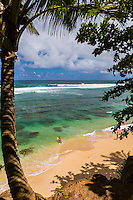 A surfer girl paddles out on the north shore of Kaua'i.