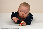 4 month old baby boy on stomach closeup playing with toy grasping with one hand and bring other hand toward toy horizontal