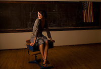 A model poses sitting on a desk in a classroom with and American flag in Maine.