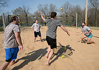 Friends Justus Bobo (from left), Gabe Skelton, Carter Wade  and Daniel Wenger play a game of Spike Ball Friday, April 2, 2021, in the sand volleyball courts at Veterans Park in Fayetteville. The game shares qualities of volleyball as members of each team bounce the ball off of the net in the center. Visit nwaonline.com/210403Daily/ for today's photo gallery. <br /> (NWA Democrat-Gazette/Andy Shupe)