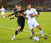 LOS ANGELES, CA – July 16, 2011: Chris Birchall (8) of the LA Galaxy  and Raphael Varane (19) during the match between LA Galaxy and Real Madrid at the Los Angeles Memorial Coliseum in Los Angeles, California. Final score Real Madrid 4, LA Galaxy 1.