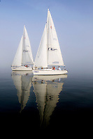 Sailboats are reflected in the water as tourists sail along the Cooper River in Charleston, SC.