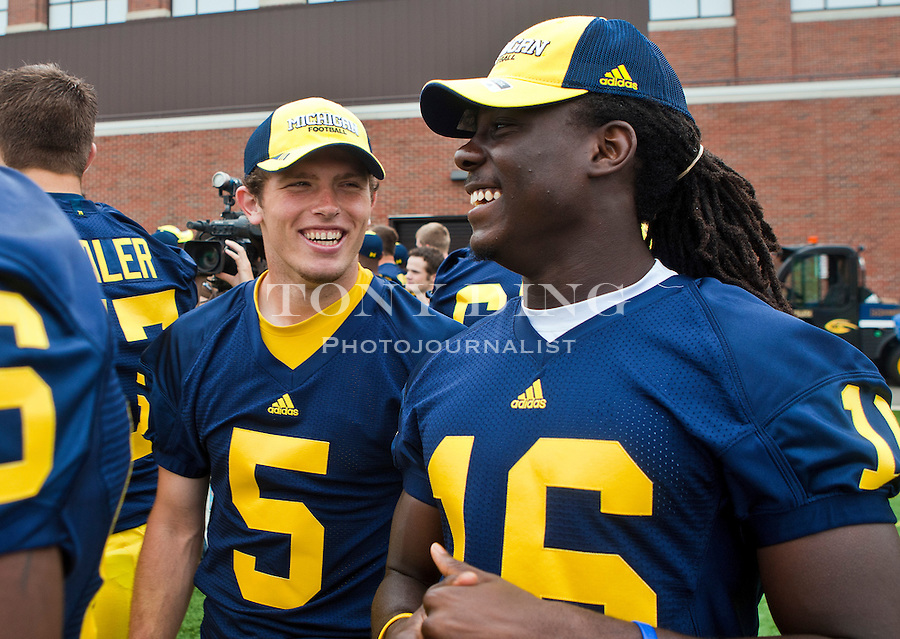 Michigan's Tate Forcier (5) jokes with fellow quarterback Denard Robinson (16), at the annual NCAA college football media day, Sunday, Aug. 22, 2010, in Ann Arbor, Mich. (AP Photo/Tony Ding)