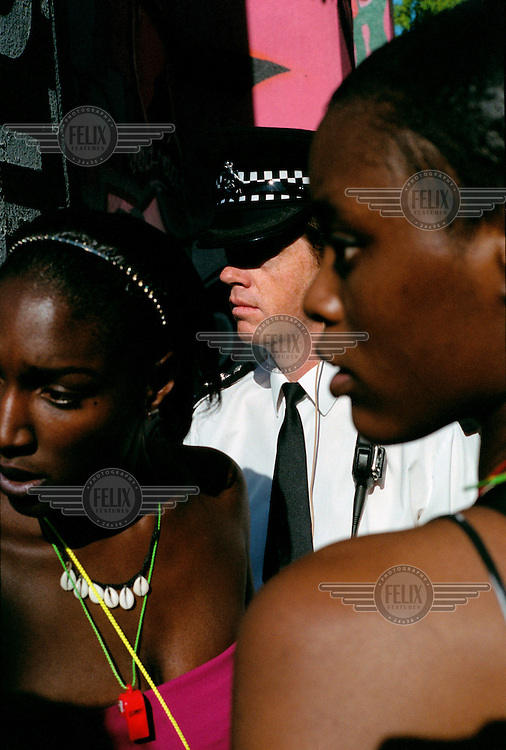 A policeman seen through two young women in the Notting Hill area of London.