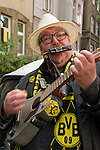 A musician and fan of the soccer club BVB 09 performing on the street. BVB won the title in the German Premium League.