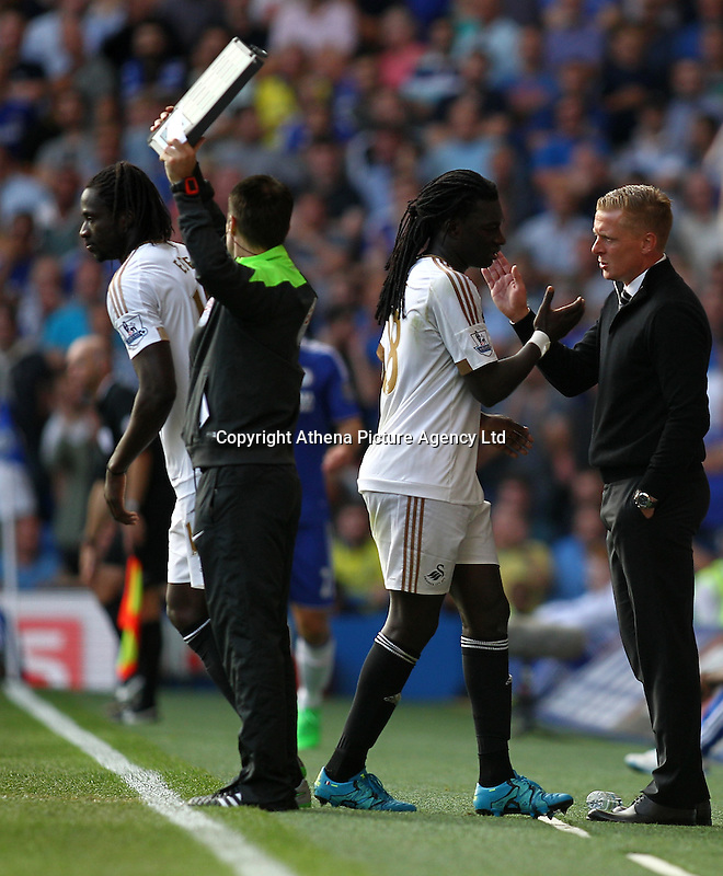 Garry Monk manager of Swansea sjakes hands with Bafetimbi Gomis of Swansea   during the Barclays Premier League match between  Chelsea and Swansea  played at Stamford Bridge, London
