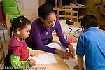 Education preschool 4 year olds art activity female teacher pointing to letters on boy's drawing as nearby girl looks and listens horizontal