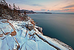 View of the snow-covered granite cliffs from Otter Point with Gorham Mountain, the Beehive, and Great Head in the distance on Mount Desert Island, Acadia National Park, Maine, USA
