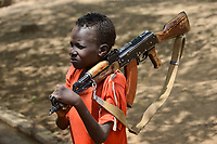 ETHIOPIA, Southern Nations, Lower Omo valley, Kangaten, village Kakuta, Nyangatom tribe, boy with machine gun Kalashnikov AK-47 for protection from cattle raids by hostile neighbor Turkana warriors, the gun is marked with SSPSHQ South Sudan Police Headquarter  / AETHIOPIEN, Omo Tal, Kangaten, Dorf Kakuta, Nyangatom Hirtenvolk, Junge traegt Maschinengewehr Kalaschnikow AK-47 zum Schutz vor Ueberfaellen durch Turkana Krieger, Gewehr hat Markierung SSPSHQ des Sued Sudan