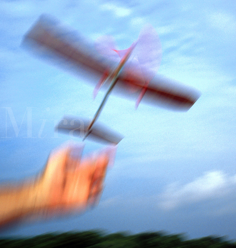 Hand launching toy airplane powered by rubber band driven propeller with red landing wheels. Balsa wood. Houston Texas.