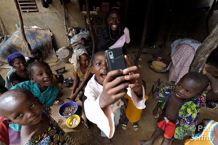 After patiently tolerating an hour of having a foreign photojournalist capture images of their daily life, internally displaced girls living in Segou, Mali, turn the tables, taking photographs of the photographer with their mobile phone.