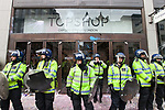"""© Joel Goodman - 07973 332324 . 26/03/2011 . London , UK . Police guard the entrance of a branch of Topshop at Oxford Circus which has paint splattered on its doorways . Hundreds of thousands of people attending an anti cuts demonstration under the banner """" March for the Alternative """" in central London , in protest at the coalition government's austerity measures . Photo credit : Joel Goodman"""