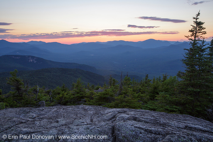 Silhouette of mountains at sunset from Middle Sister Mountain in Albany, New Hampshire during the summer months.